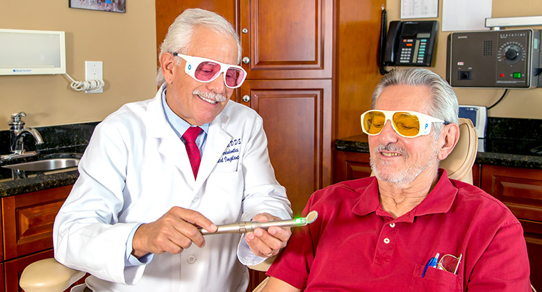 doctor showing patient the lights used to detect oral